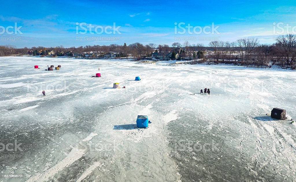Ice fishing on a warm winter day stock photo