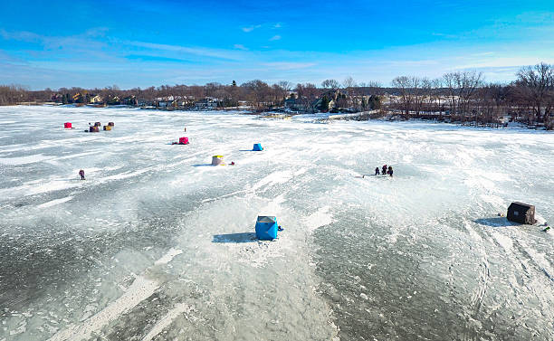 ice fishing on a warm winter day - green bay wisconsin stock photos and pictures
