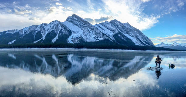 Ice fishing on frozen mountain lake stock photo