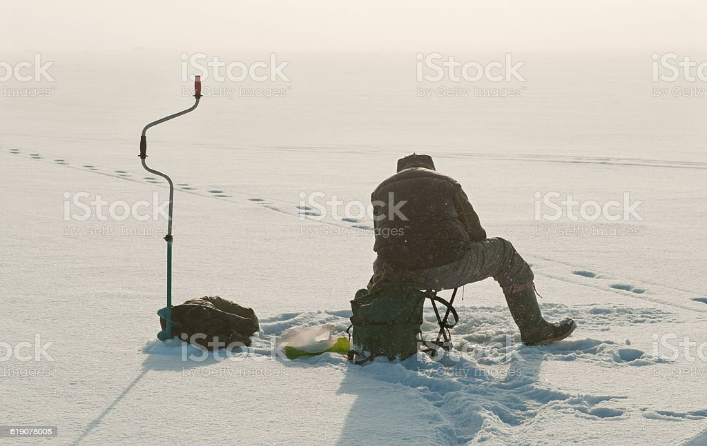 Ice fishing on the lake. stock photo