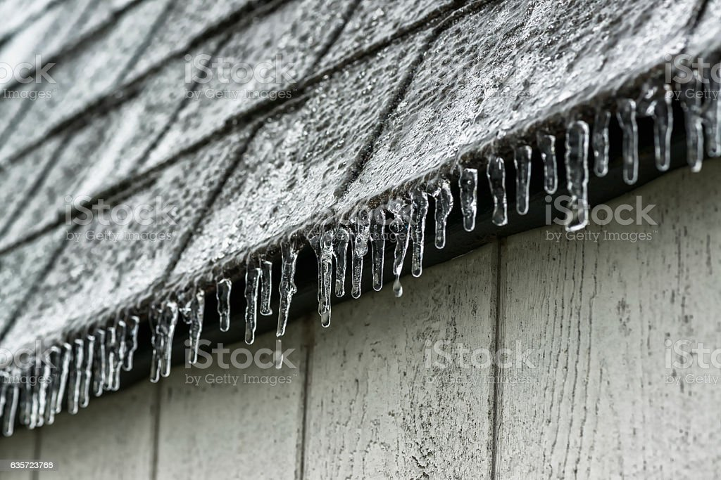 Ice forming on the edge of the roof shingles stock photo