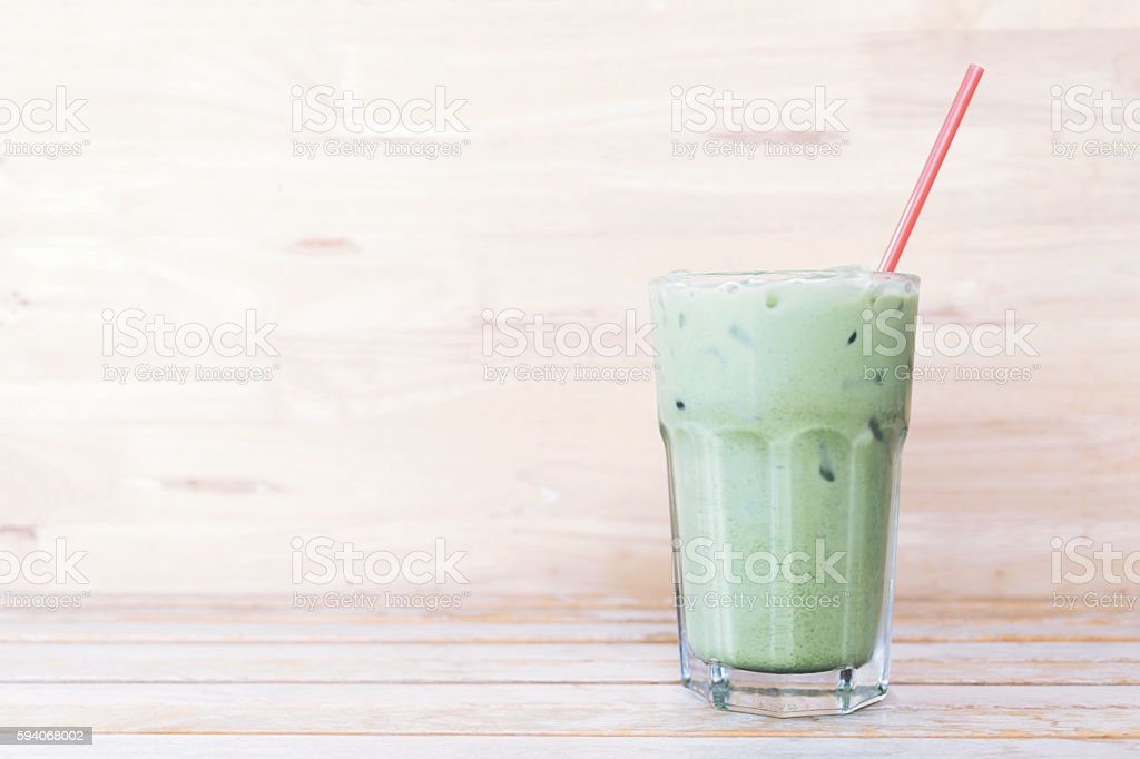 ice green tea (matcha)with a red straw on wood background stock photo