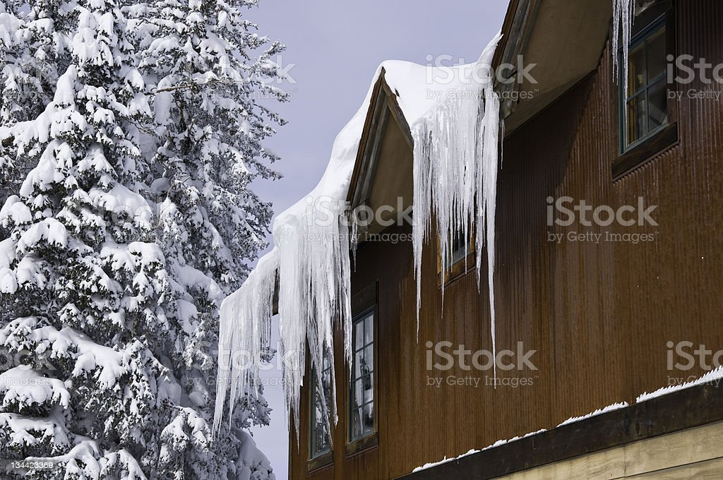 Ice Hanging from Home Roof in WInter royalty-free stock photo