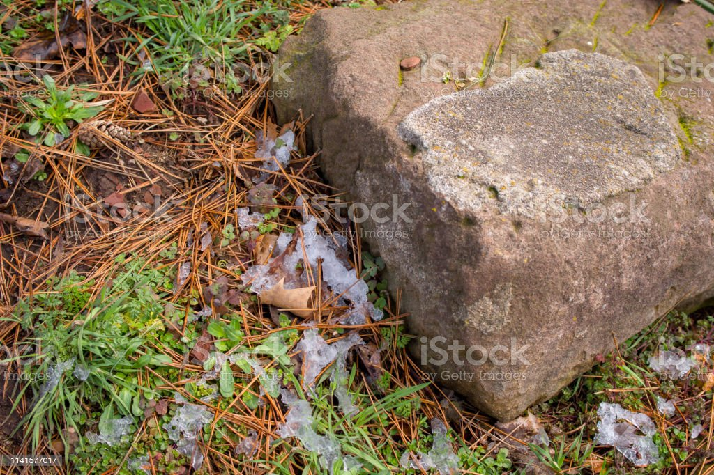 Ice hides in the shadows of a rock stock photo