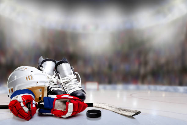 ice hockey helmet, skates, gloves, stick and puck in rink - hockey stick stock pictures, royalty-free photos & images