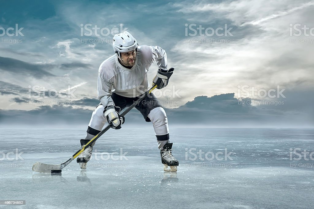 Ice hockey player on the ice in mountains stock photo