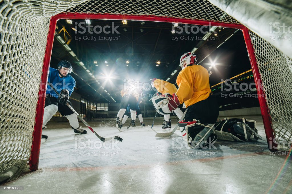 Ice hockey player taking a shoot and scoring during the game. The...