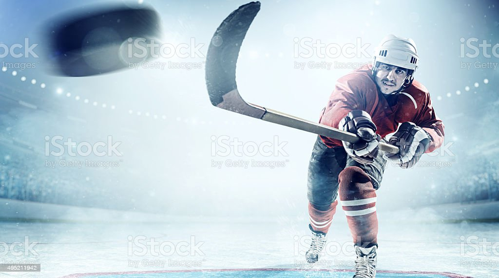 View of professional ice hockey player scoring during game in indoor...
