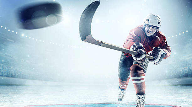ice hockey players in action - hockey puck stock photos and pictures