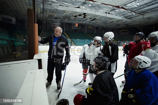 Group of female ice hockey players standing on the ice in a huddle around their coach as he teaches them strategy. They are all looking toward the board where he is writing and drawing different positions.