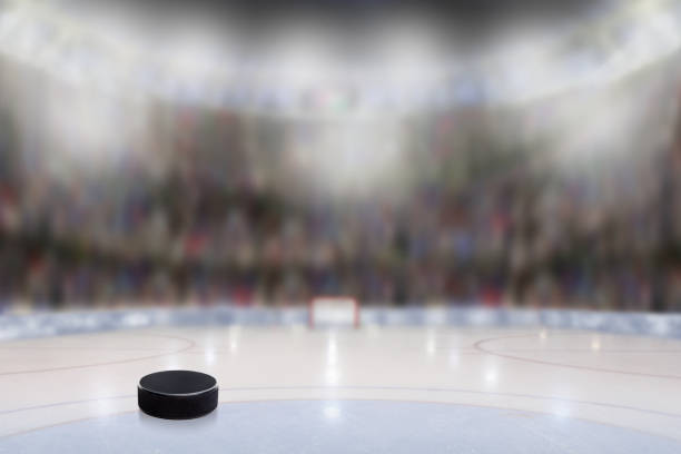 ice hockey puck in rink arena with copy space - hockey stock pictures, royalty-free photos & images