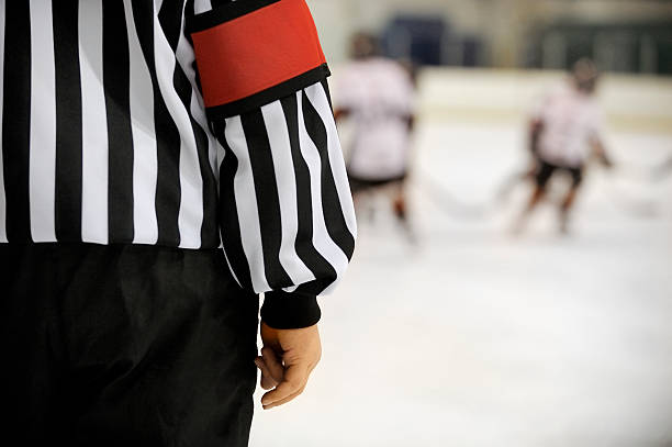 Ice hockey referee Ice hockey referee in front of players with copy space.Click on an referee stock pictures, royalty-free photos & images