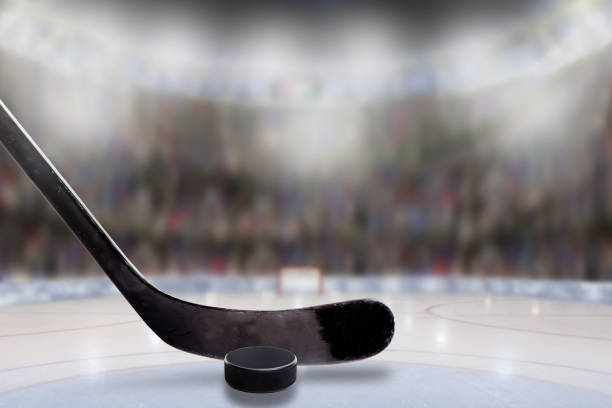 ice hockey stick and puck in rink with copy space - hockey puck stock photos and pictures