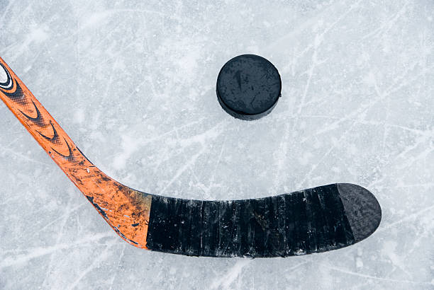 ice hockey stick and puck on ice - hockey puck stock photos and pictures
