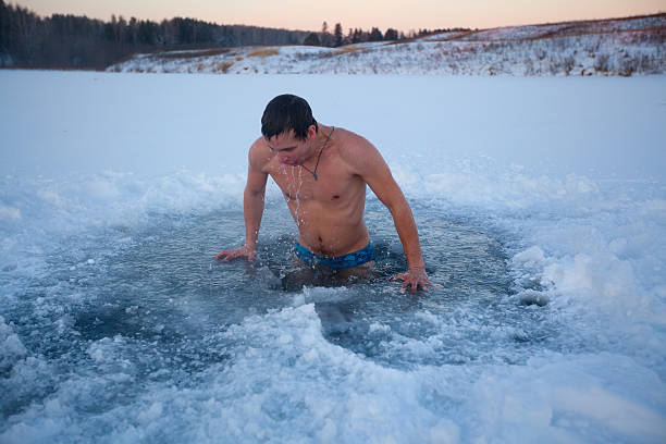 Ice hole Young man having recreational swim in the ice hole taking the plunge stock pictures, royalty-free photos & images