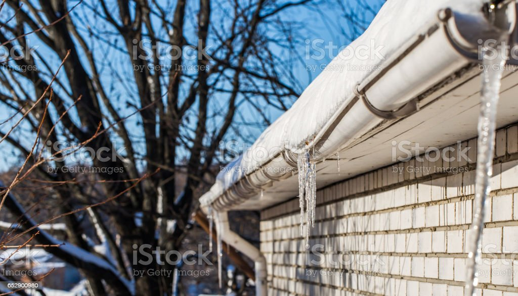 ice icicles on the roofs of houses stock photo