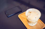 Ice Macchiato coffee with smart phone on the table in coffee shop. Selective focused at smartphone.