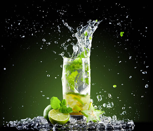 Ice mojito drink with splash Studio shot of fresh mojito drink with ice cubes and splash on black background mojito stock pictures, royalty-free photos & images