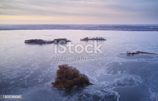 Ice on lake with small islands aerial drone view