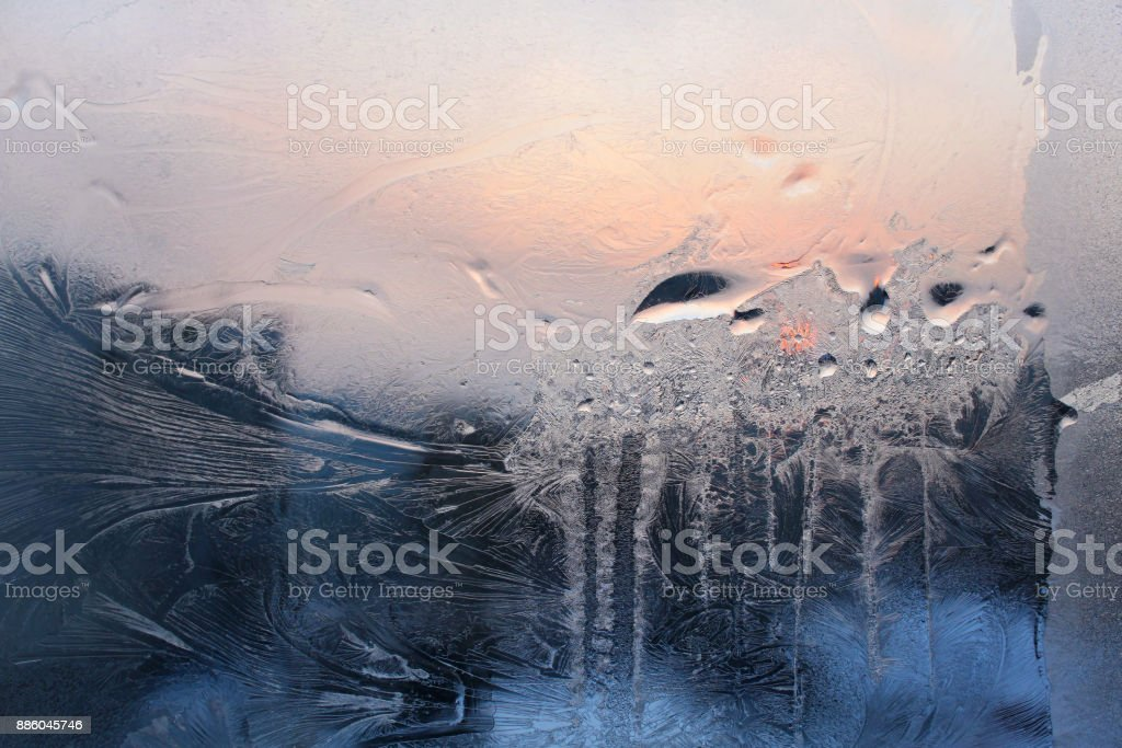 Ice pattern, water drops and morning sunlight on winter window glass stock photo