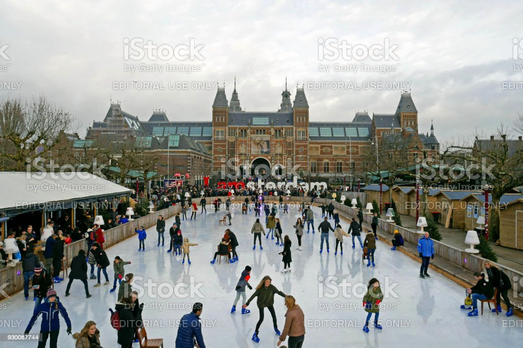 Ice rink during the winter at Museumplein. In the background you can see the Rijksmuseum with words I Amsterdam. stock photo