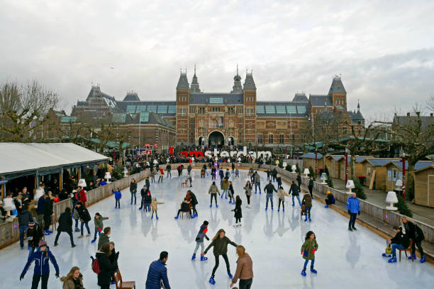 Ice rink during the winter at Museumplein. In the background you can see the Rijksmuseum with words I Amsterdam. Amsterdam / Netherlands - January 1 2018: Panorama of the ice rink during the winter at Museumplein. In the background you can see the Rijksmuseum with words I Amsterdam. museumplein stock pictures, royalty-free photos & images