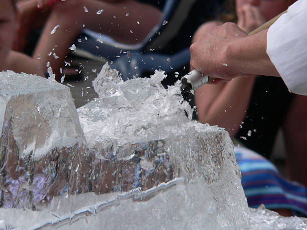 Ice sculptor chiseling a creation from a block of ice stock photo