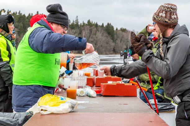 Ice skaters and an older volunteer serving drinks at a rest area. stock photo