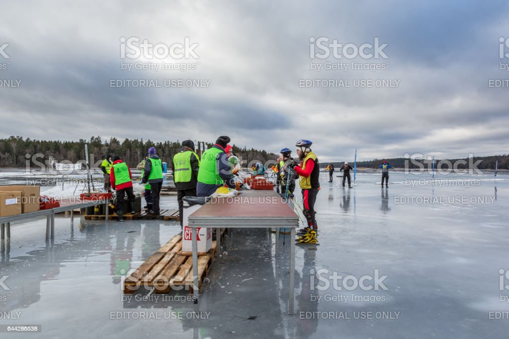 Ice skaters at a rest area taking a break and voluntary workers serving drinks. stock photo