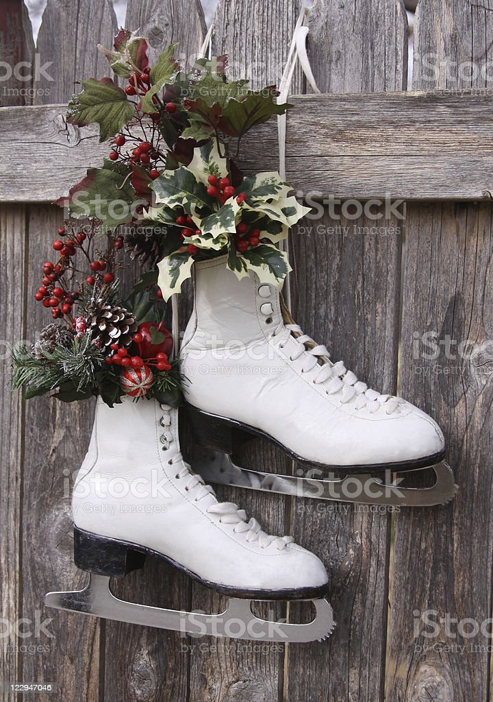 Ice Skates Hanging on Fence with Holly stock photo