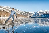 Beautiful woman ice skating on the frozen lake Grundlsee in front of a stunning Alps panorama. Nikon 810. Converted from RAW.