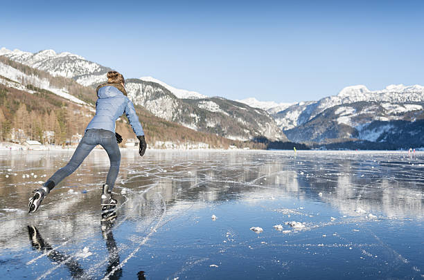 Ice Skating, Frozen Lake Grundlsee, Austria Beautiful woman ice skating on the frozen lake Grundlsee in front of a stunning Alps panorama. Nikon 810. Converted from RAW. ice skating stock pictures, royalty-free photos & images