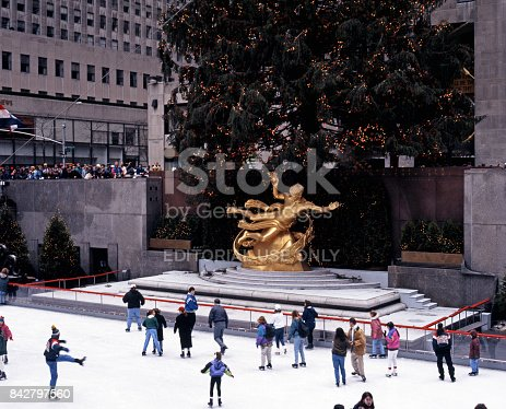 People skating on the ice rink and Prometheus statue in the Rockefeller Plaza at Christmas, New York, USA.