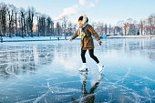 Ice skating on the frozen lake. Young woman on ice skates in sunset.