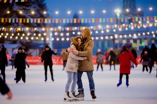 Ice skating rink and lovers together. A pair of young people in an embrace on a city skating rink lit by light bulbs and bright lights. Winter date for Christmas on the ice arena Ice skating rink and lovers together. A pair of young, stylish people in an embrace in a crowd on a city skating rink lit by light bulbs and bright lights. Winter date for Christmas on the ice arena ice skating stock pictures, royalty-free photos & images