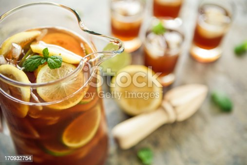 A jug and four glasses of fresh homemade ice tea.