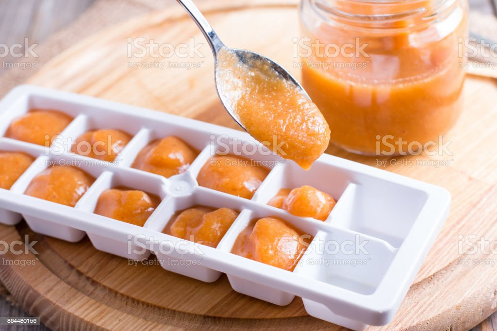 Ice tray with fresh fruit puree on wooden background stock photo