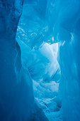 A tunnel in Franz Josef Glacier, South Island, New Zealand. Surrounded by blue ice.