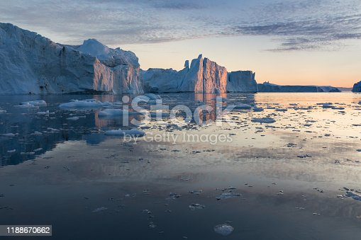 Disko Bay during midnight sun Ilulissat, Greenland. Studying of a phenomenon of global warming Ices and icebergs. Beautiful background landcape concept