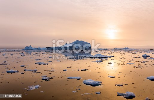Iceberg in Greenland on a beautiful evening in the sunset magical natural light.