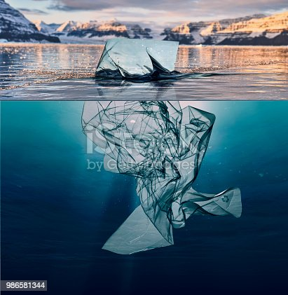 iceberg of garbage plastic floating in ocean with greenland background