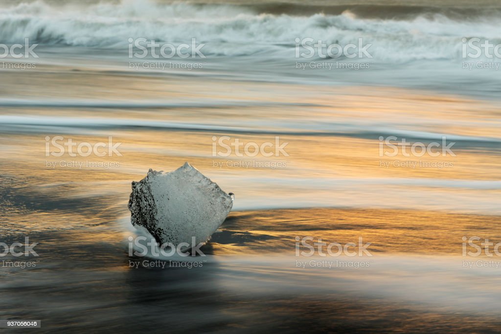 Iceberg on black sand beach with heavy waves passed in early morning at Diamond beach in Jokulsarlon lagoon South Iceland,Famous travel destinations. stock photo