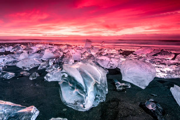 Iceberg on Jokulsarlon glacial lagoon beach An iceberg along the shore of Jokulsarlon glacial lagoon during a vibrant red sunrise rests motionless as it is framed by cold ocean water. jokulsarlon stock pictures, royalty-free photos & images