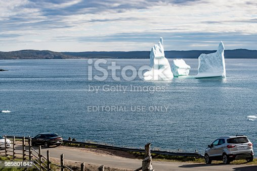 Newfoundland and Labrador, Canada - June 7, 2018: Tourists parking on the roadside are watching icebergs at Wolf Cove in Canada.