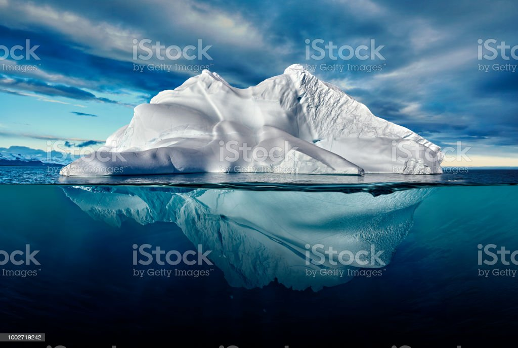 iceberg with above and underwater view taken in greenland. iceberg with above and underwater view taken in greenland Above Stock Photo