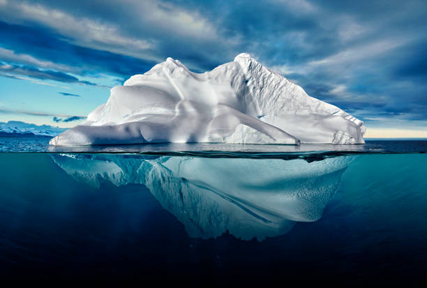 iceberg with above and underwater view taken in greenland. - abaixo imagens e fotografias de stock