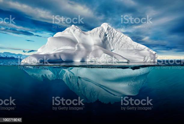 Photo of iceberg with above and underwater view taken in greenland.