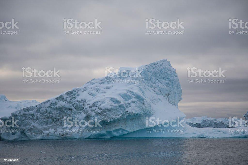 iceberg with cloudy sky stock photo
