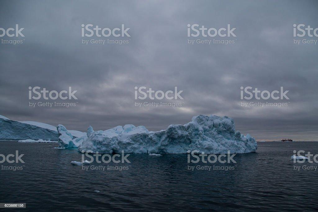 iceberg with dark clouds and icebreaker stock photo