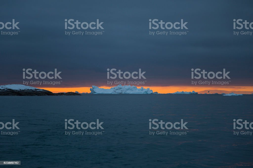Iceberg with sinister sky and epic sunset stock photo